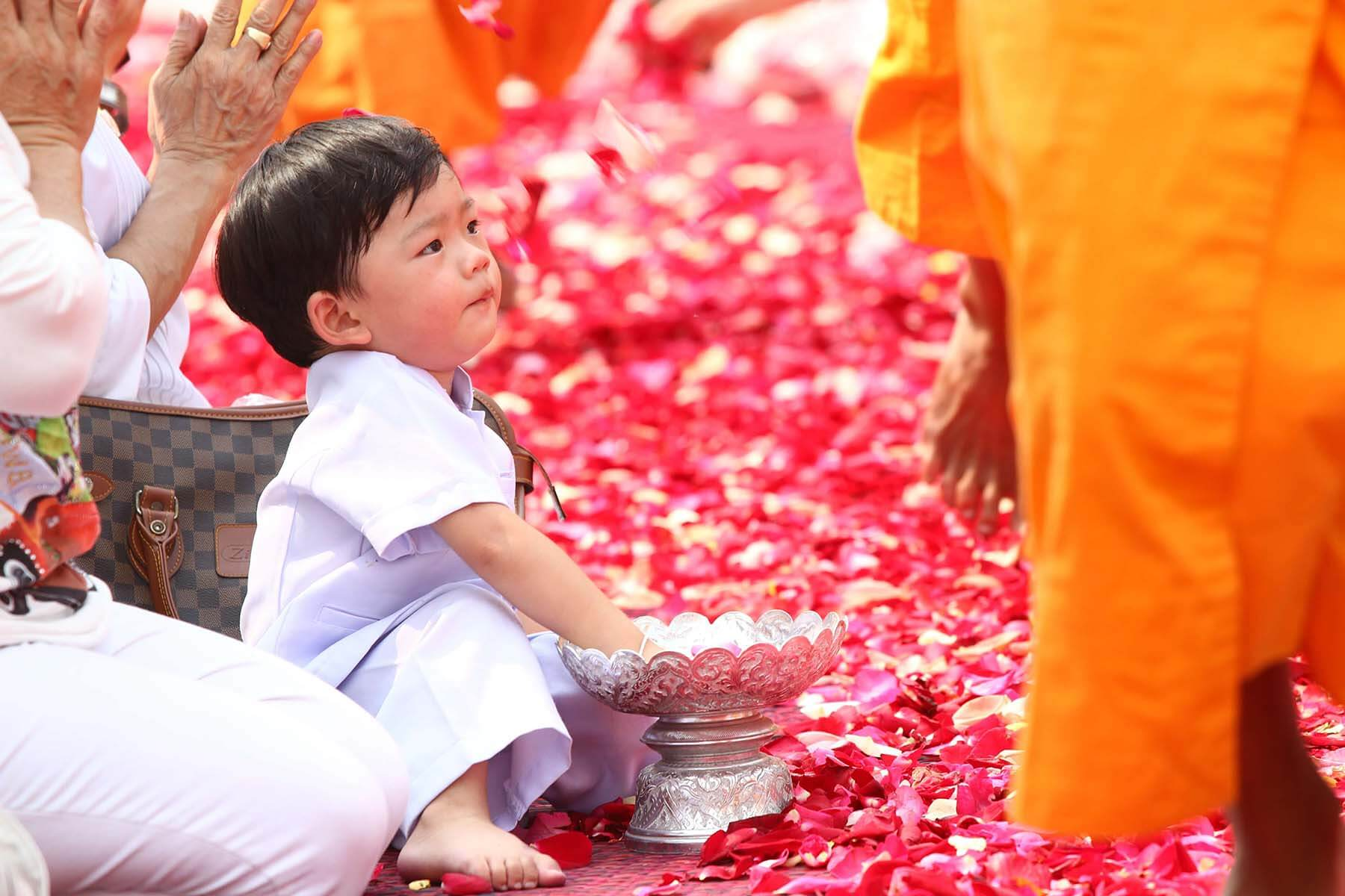 Toddler surrounded by flowers at Buddhist festival.